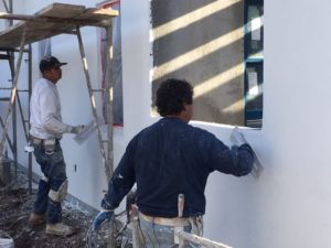 Painters applying the white coat on the wall